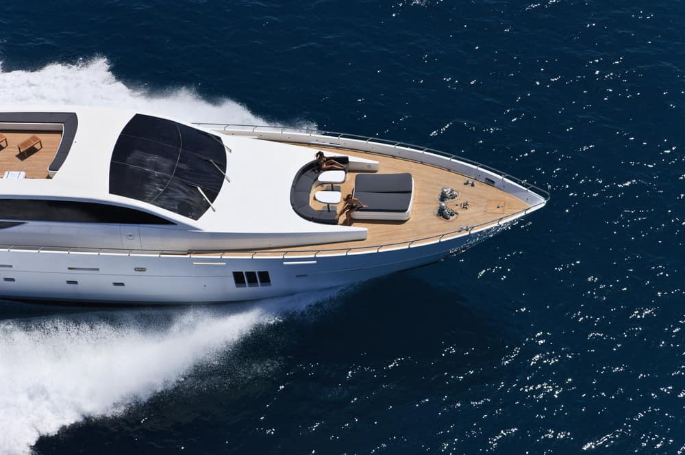 Aerial view of the bow deck and partial view of the flybridge deck on yacht speeding on ocean.