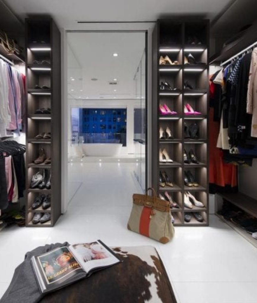 The closet is accessible from the bathroom and is offering multiple cabinets and shoes storage.