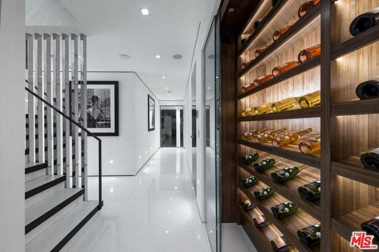 A sleek white house with hints of black features a custom wine cellar with wood shelves and glass door.