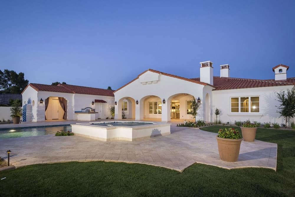 The home's backyard include a tiled flooring surrounded by well-maintained lawn along with a swimming pool.