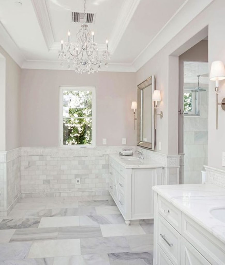 The bathroom is complete with a deep soaking tub and a walk-in shower room lighted by a set of wall lights and chandelier backed up by sinks equipped with marble countertop.
