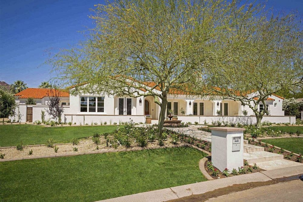 The frontyard of the house features beautiful landscaping trees and lawn.