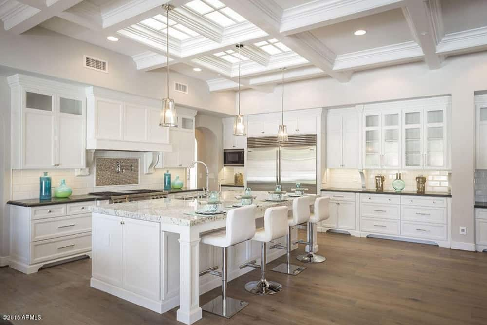 White kitchen with a stylish breakfast bar lighted by classy pendant lights hanging from the coffered ceiling. The room also features hardwood floors.