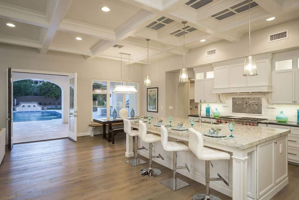 Spacious white kitchen features a dining nook beside the breakfast island topped with a marble counter. It has a built-in bench and wooden dining table illuminated by a pendant light that hung from the coffered ceiling.