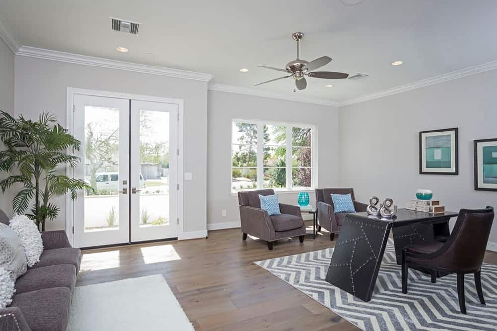 The home features a home office with a small living space equipped by contemporary furniture.