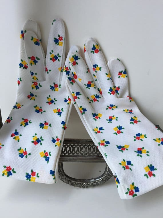 White garden gloves made out of nylon, enhanced with floral designs.
