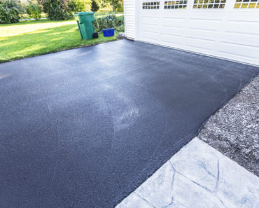 Newly poured asphalt driveway for house in the suburbs