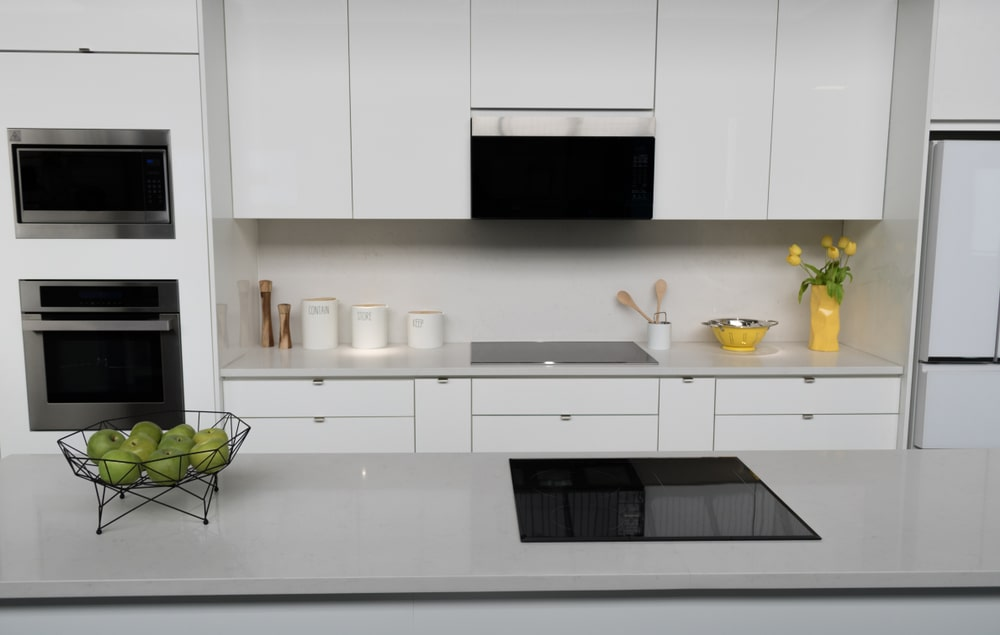 A modern kitchen with quartz countertops and white modern cabinetry.