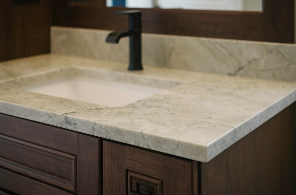 This is a close look at a small bathroom vanity with quartz countertop and backsplash.