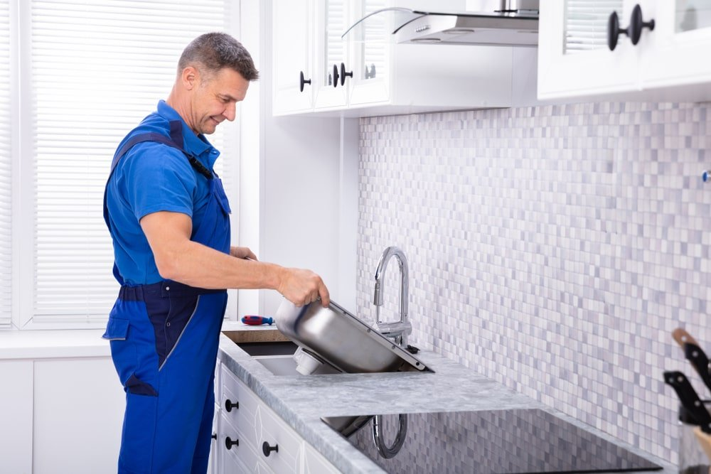 A man installing a sink to the kitchen with quartz countertops.