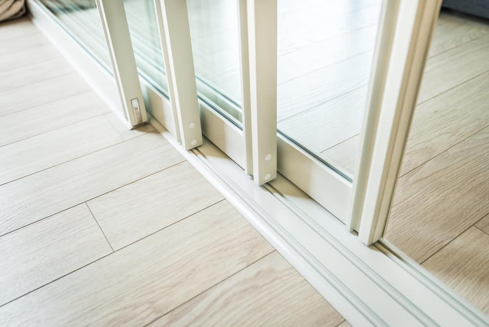 Close up photo of a stacker door in a home leading to a patio