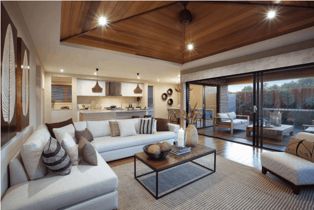 Large living room with huge glass window and stacker doors leading to covered patio