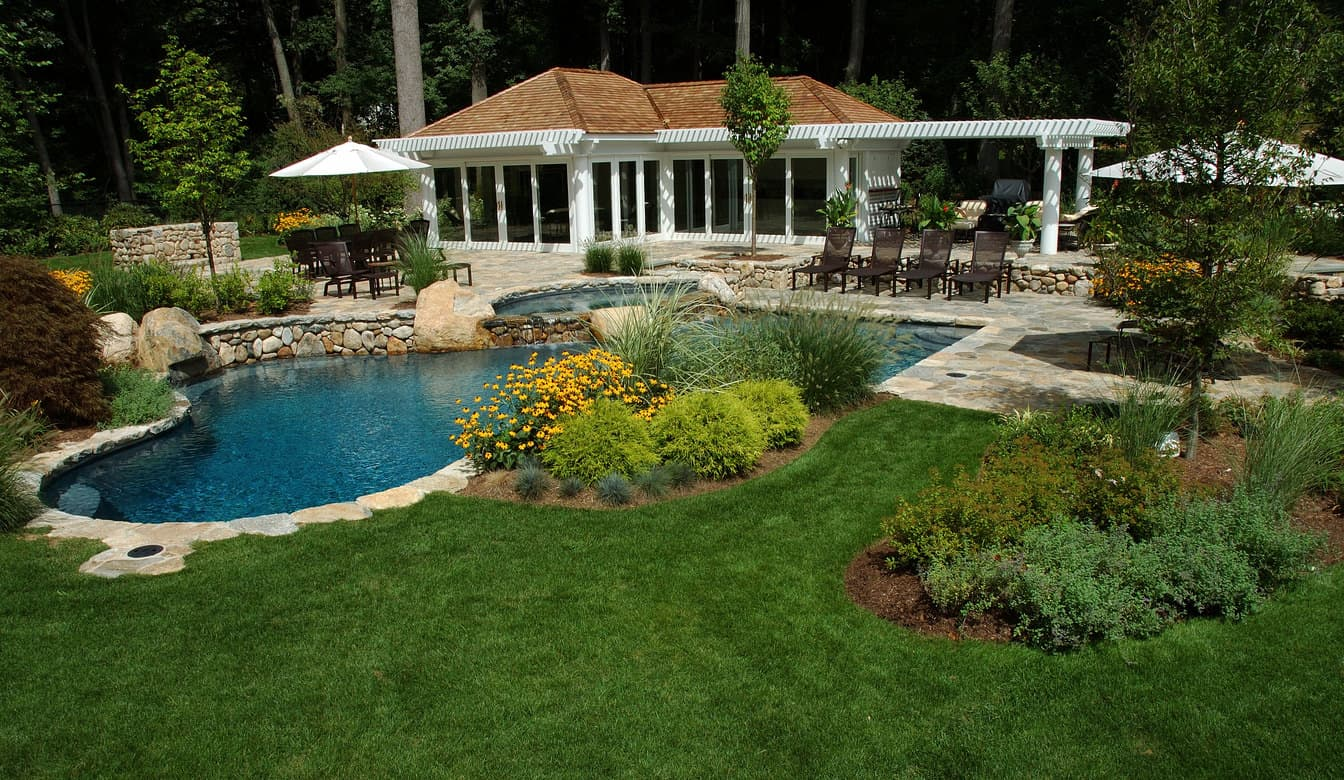 An astonishing sight of pool set in gardens with a nice pool house.