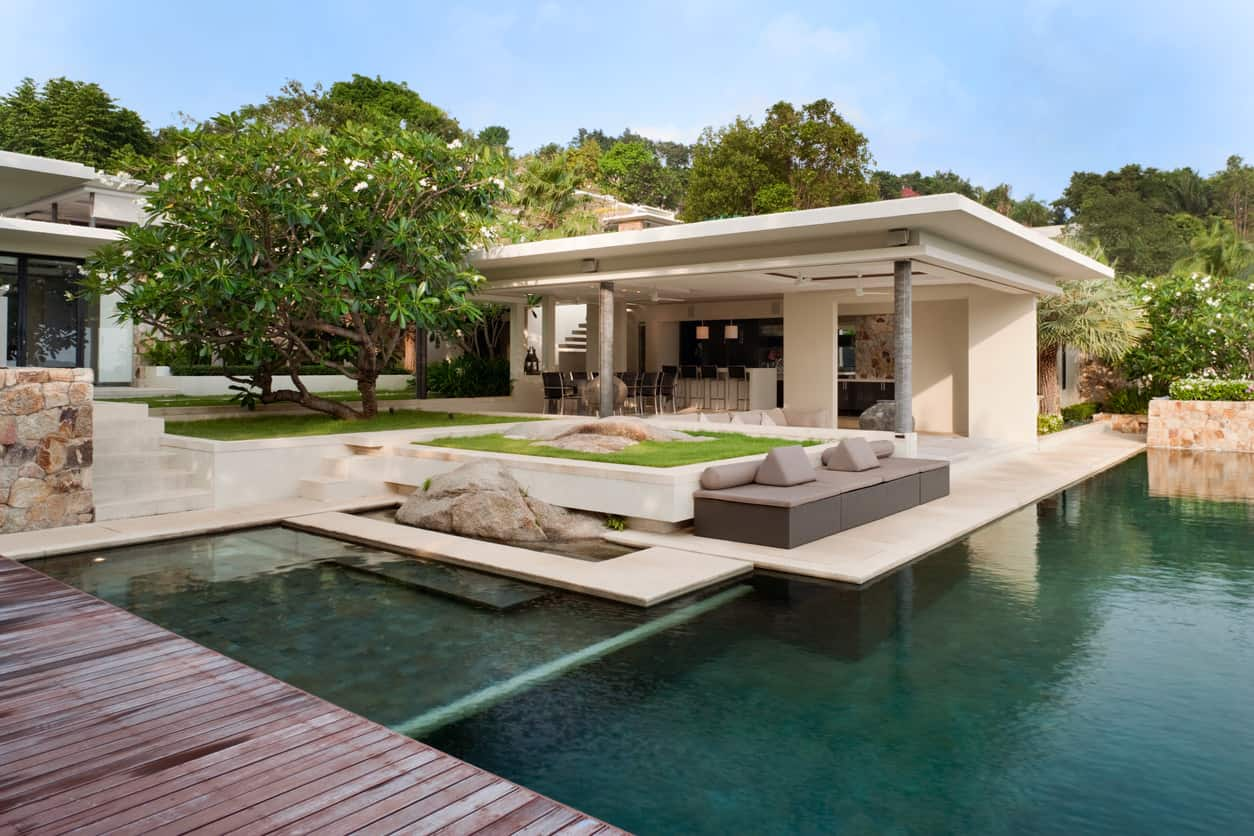 A modern house surrounded by towering and abundant trees showcases an L-shaped pool with a hot tub. It has a natural wooden deck on the side along with a gray seating topped with cylindrical and triangular <a class=