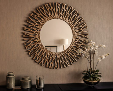 A circular mirror with a customized frame in bronze.