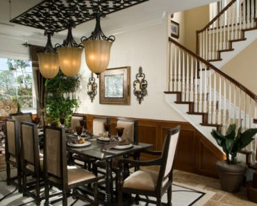 Ultra luxury dining room decor and design with dark dining room furniture, pendant lights at bottom of stairs.