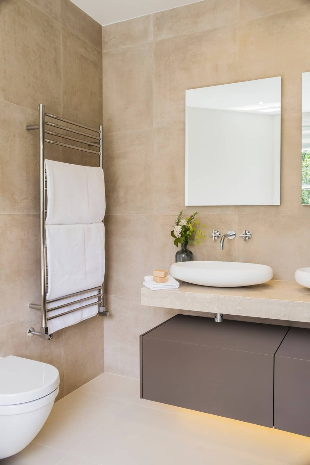 The bathroom features a double vessel sink with tiles walls and floors. Photo Credit: Rick Mccullagh