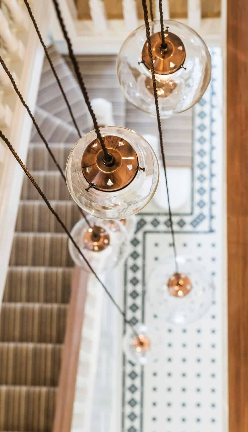 The entrance hall's staircase is lighted by a set of stylish pendant lights. Photo Credit: Rick Mccullagh