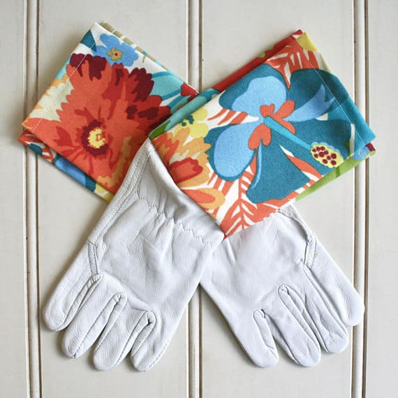 White leather gloves with colorful floral accents.