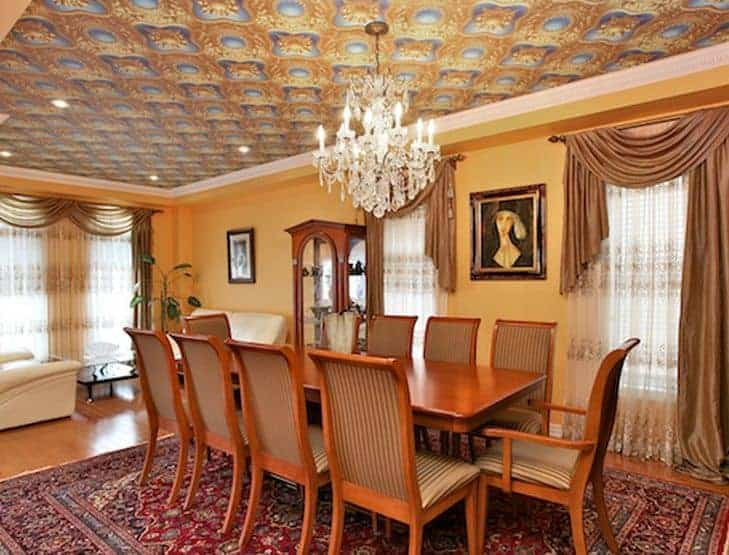 A glamorous dining room featuring a large area rug where the wooden dining table set for 10 is situated. The room is lighted by an elegant chandelier hanging from the decorated ceiling.