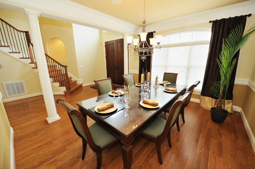 A minimalist dining area featuring hardwood flooring and yellow walls. The room offers a classy dining table set lighted by a fancy chandelier.