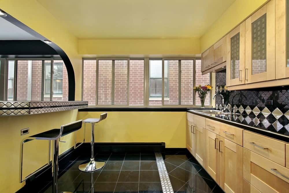 A modish kitchen style featuring black tiles flooring and black countertops. There's a bar area as well with modern bar stools.