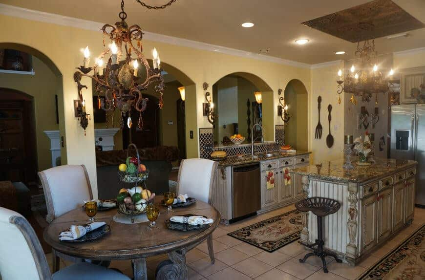 Mediterranean-style kitchen featuring a small center island and a round dining nook, both lighted by a pair of chandeliers.