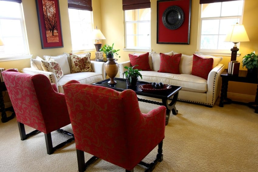 This living room boasts a beautiful set of seats, carpet flooring and yellow walls. The room is lighted by table lamps.