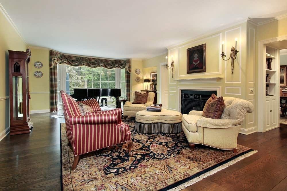 Large living room featuring a large area rug covering the hardwood flooring. The room offers a nice set of seats, a fireplace and a piano on the side near the windows.