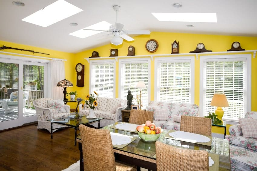 A large sunroom with beautiful seats and a glass top dining table set for four. The walls are painted in bright yellow.