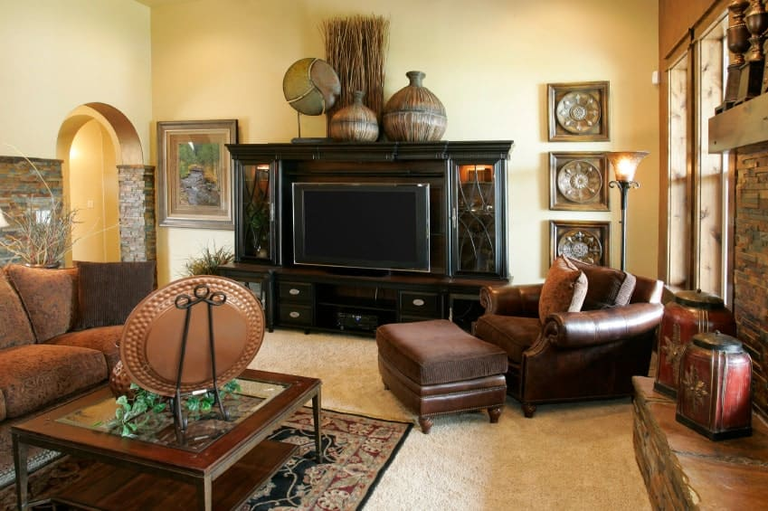A living room featuring carpet flooring and yellow walls. The area offers elegant seats along with a large TV in front.