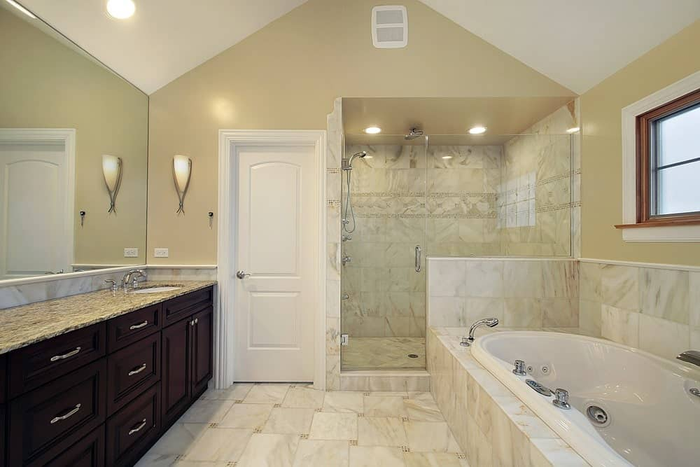 This primary bathroom boasts marble tiles flooring matching the marble walls in the corner walk-in shower and the marble platform of the deep soaking tub.