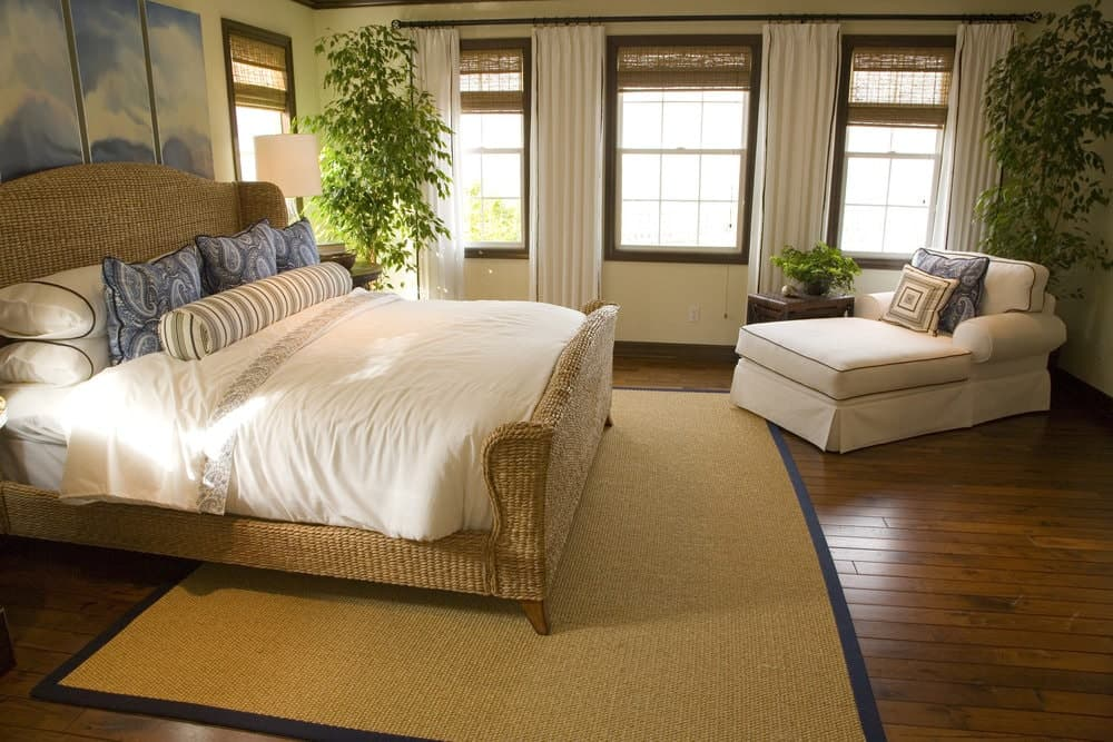 Medium-sized primary bedroom featuring hardwood flooring topped by a rug. The room offers a rattan bed frame and a comfy bed set.