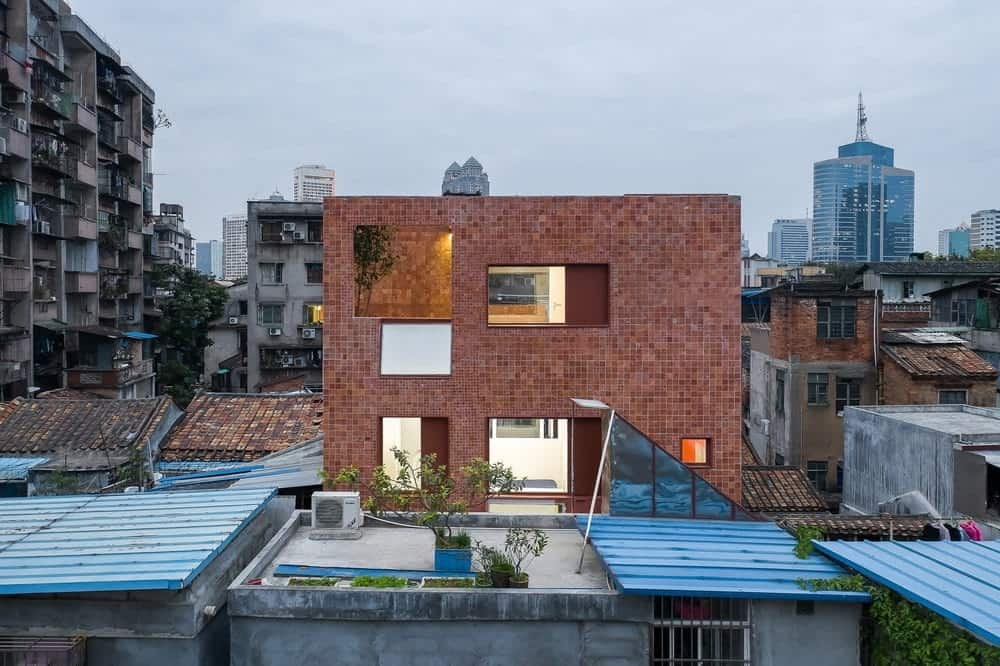 This is an exterior view of the house that has red brick exterior walls and structures complemented by the geometric designs of the windows and the warm glow that comes from the interiors of the multi-level house.