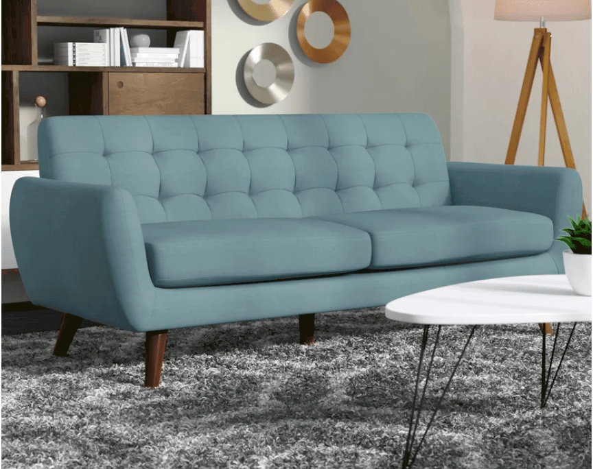 Blue mid-century style sofa with tufted back and angled narrow wood legs