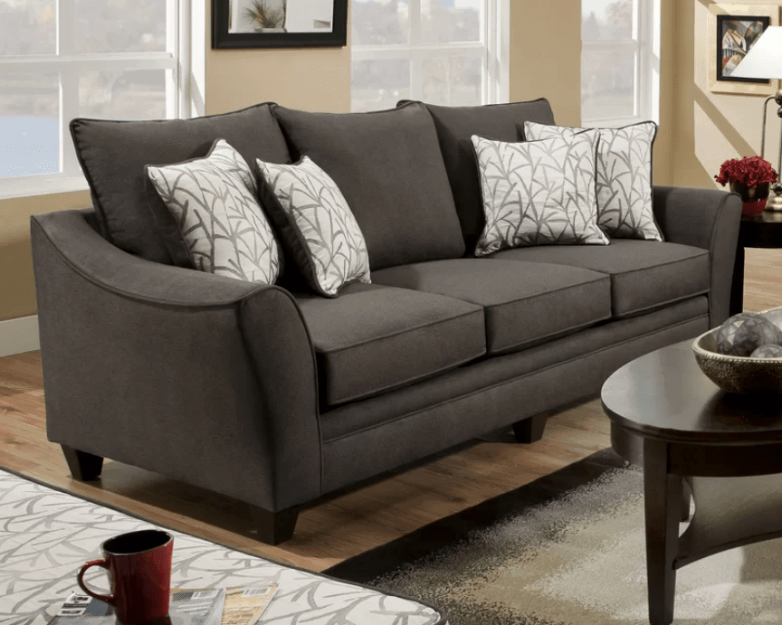 Dark brown sleeper sofa with concave arms and detachable back cushions.