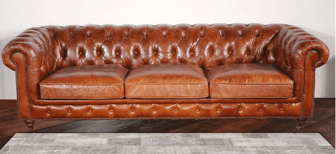 Striking rich leather chesterfield sofa with tufted back, arms and lower front.