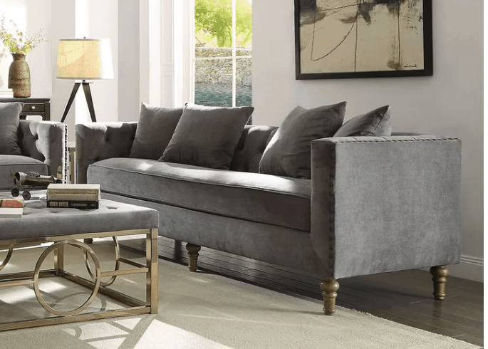 Gray sofa with high arms and long ornate wooden legs
