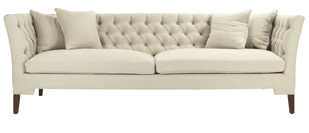 Cream colored chesterfield style sofa with elegant exposed wooden legs