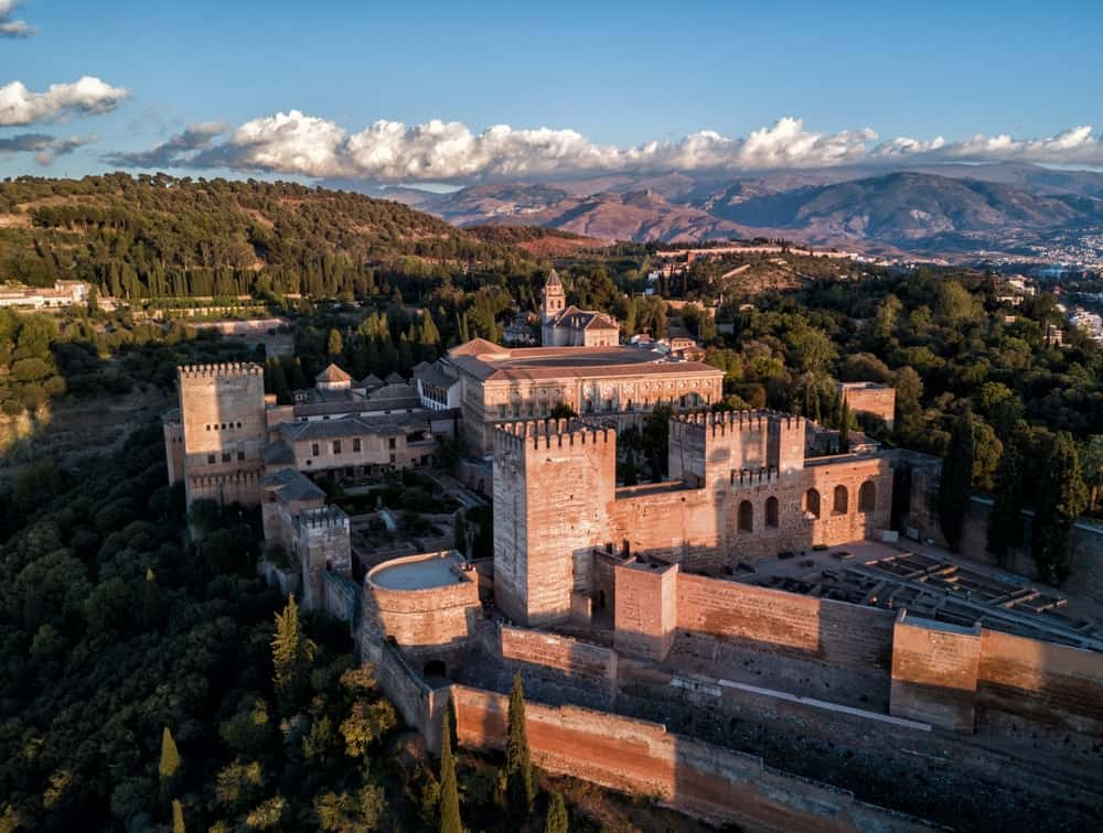 Aerial view of The Alhambra Palace, a vast castle fortress complex surrounded by autumn trees overlooking Granada, built by the Moorish Empire.