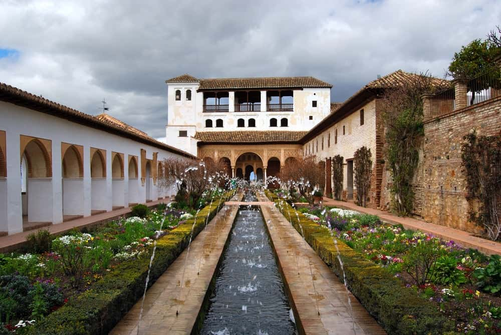 Patio de la Acequia or Court of the Water Channel with water fountain and beautiful garden, Granada, Spain.