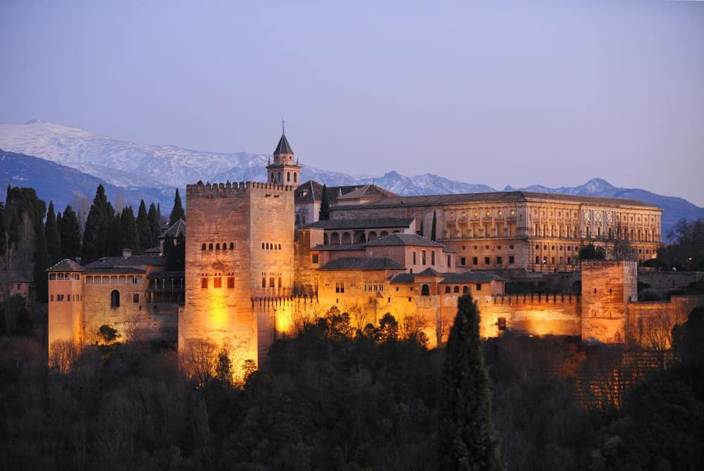 The Palace of Alhambra with Comares Tower, Palace of Charles V and Sierra Nevada at background during sunset, Granada, Andalusia, Spain.