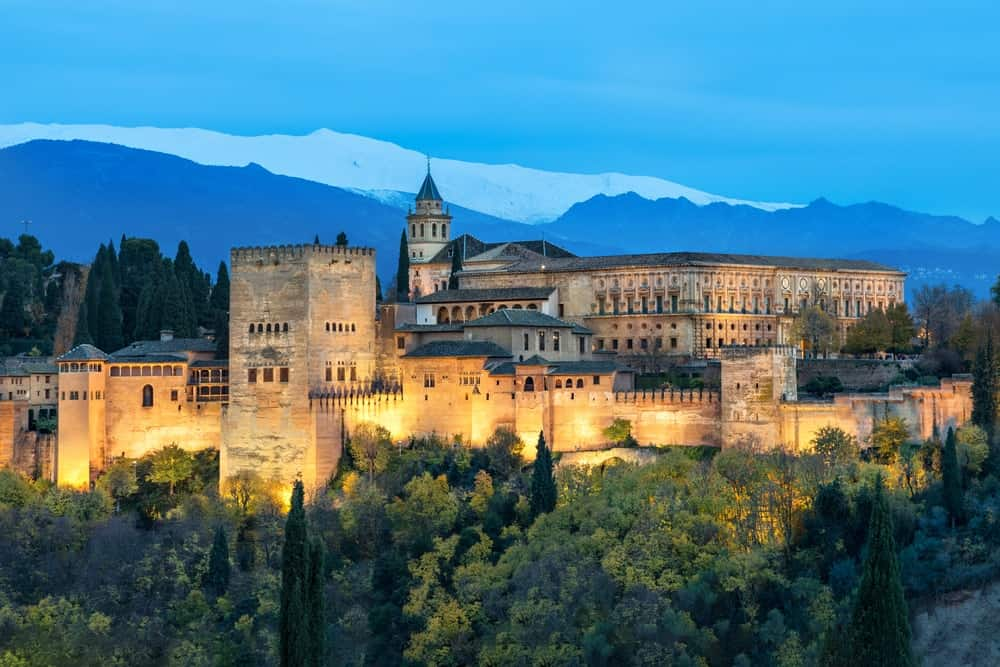 Alhambra, a medieval Moorish fortress surrounded by yellow autumn trees illuminated in the evening of Granada, Andalusia, Spain.