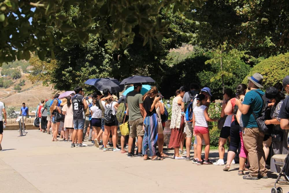 Tourists fall in line to enter the famous Nasrid Palaces (Palacios Nazaries) at Alhambra palace and fortress complex.