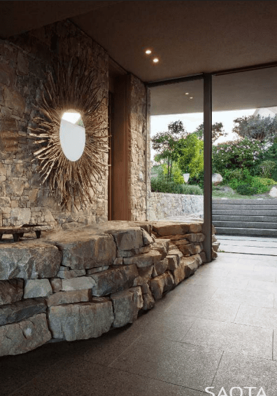 The home's hallway featuring stone walls and elegant mirror. Photo Credit: Adam Letch
