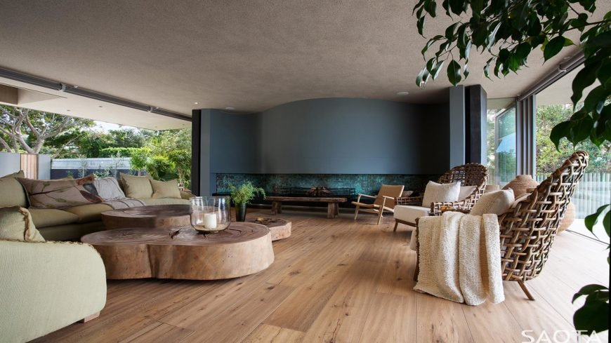 Magnificent living room with panoramic windows and wood plank flooring that complements with the modular coffee table and bench. It has a fabulous accent wall fitted with a firewood fireplace.