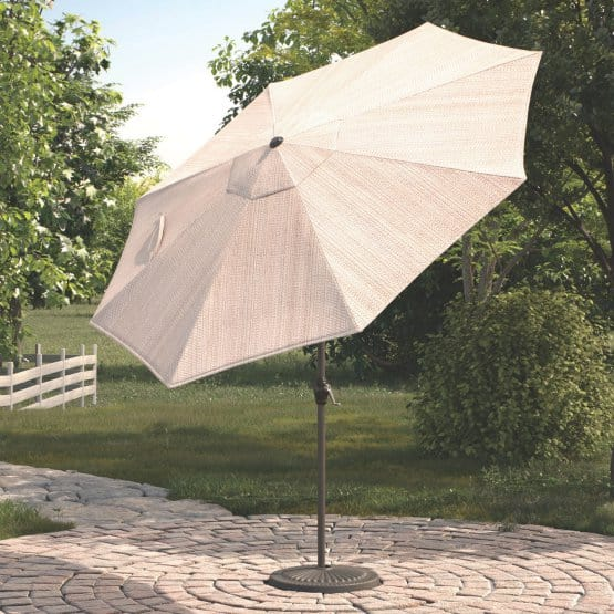 A beige, tilting patio umbrella made out of polyester fabric.