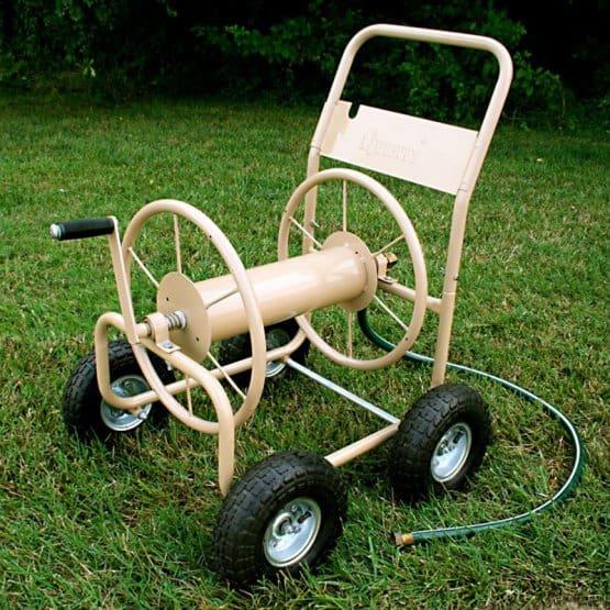Beige, four-wheeled cart with hose storage.