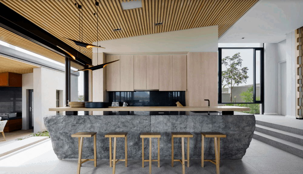 An open kitchen illuminated by stylish black pendants that hung from the wood plank ceiling. It has light wood cabinetry and natural stone kitchen island topped with a wooden counter.