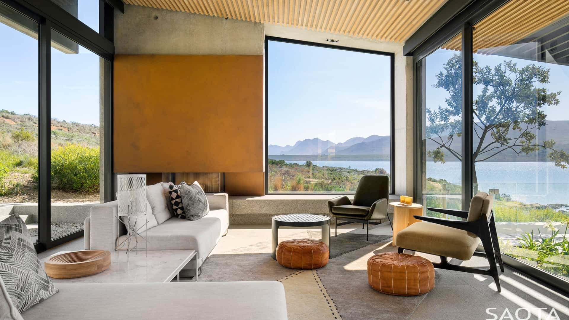 The living room features modern furniture and glass walls overlooking the beautiful outdoor view. Photo Credit: Adam Letch